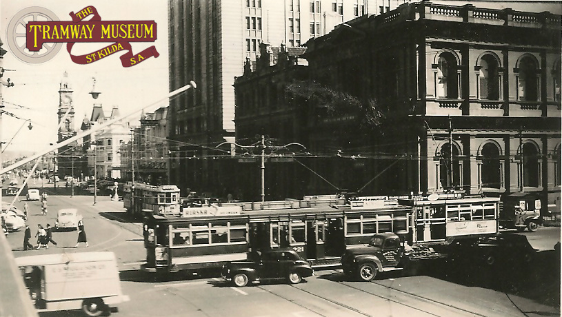 A busy 1954 scene at the intersection of King William Street/Grenfell Street/Currie Street. Two 'Drop Centre' trams are crossing over King William Street bound for both the eastern and western suburbs while a third 'Drop Centre' waits for its' turn to cross the intersection bound for one of the northern suburbs. Trams would eventually return to this part of King William Street in 2007.