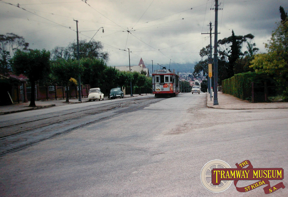 F1 type 'Drop Centre' tram 283 is seen climbing to the top of Smith Street in Walkerville with a service to Walkerville North. Beneath the central cab window is a sign showing that this tram will be making a connection with a Gilles Plains bound bus service. Photo: Keith Kings.