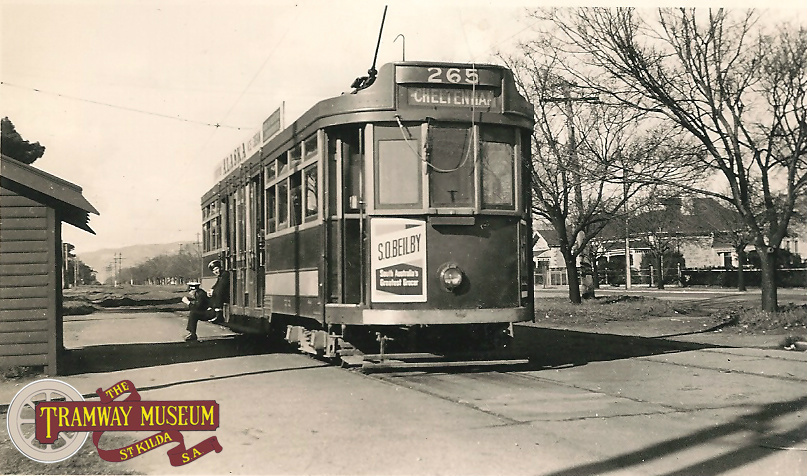 F1 type tram 265 at the Wayville West terminus at the intersection of Greenhill Road and Anzac Highway while the tram crew wait on the footboard at the quiet terminus for departure time and the long journey to Cheltenham, July 1951.