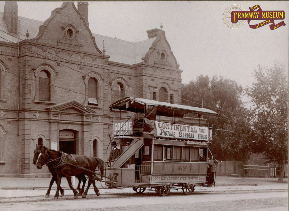 A standard Adelaide and Suburban Tramway Company double deck horse tram passing the City Baths (now the site of the ADELAIDE Festival Centre) on King William Road.