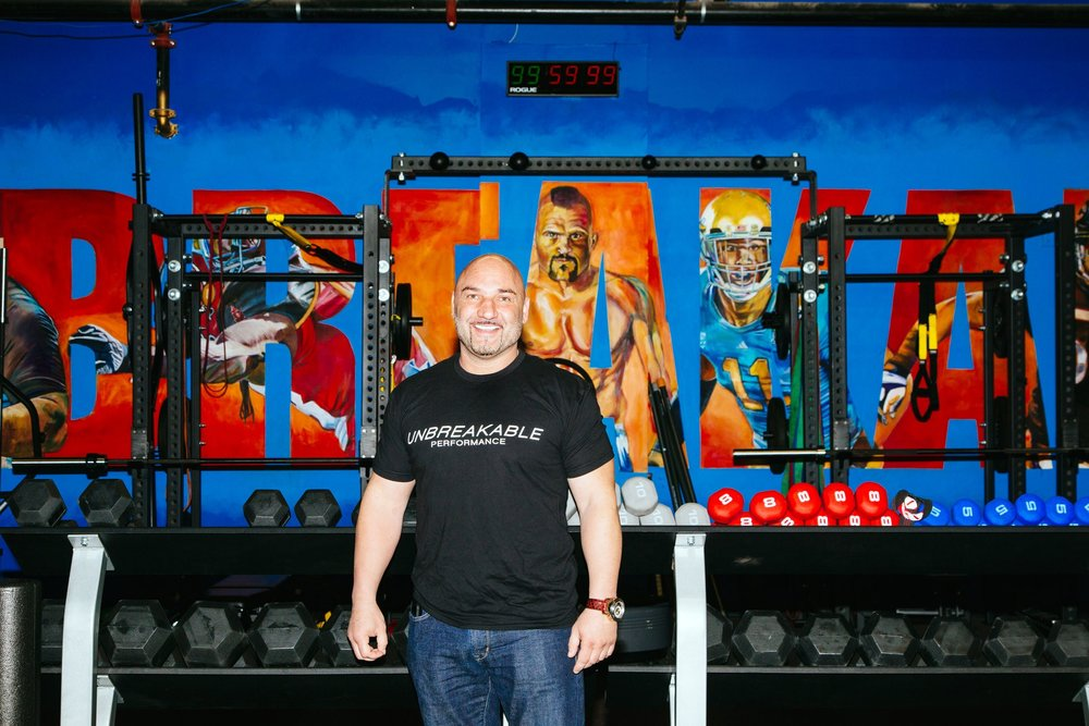 Jay Glazer, Unbreakable's impresario, in front of a mural depicting some of the gym's owners. Credit Kendrick Brinson for The New York Times