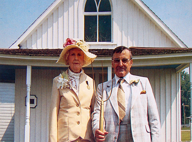 Nan Wood Graham, the model for the woman in  American Gothic  and Wood's sister, poses with Carl E. Smith, the owner of the house at the time, in front of the Dibble House, now known as the American Gothic House.
