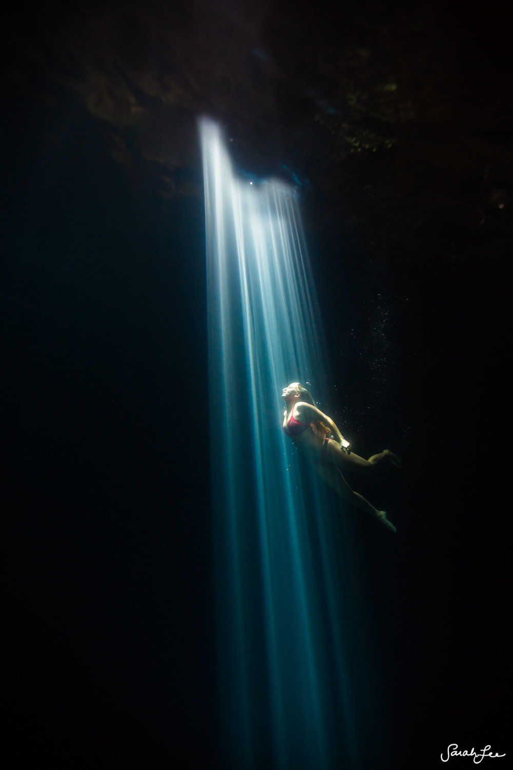 Spectacular light rays created naturally by the sunlight at high noon as it hit one single opening in the roof of this cenote.