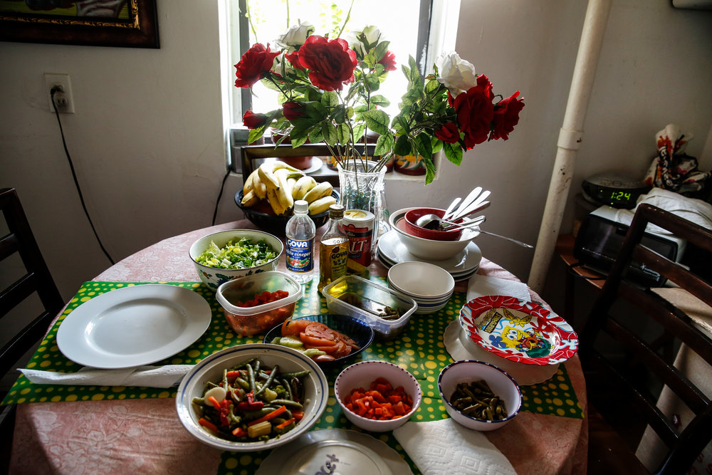 Maria Rodriguez's apartment sparkles; it's a warm and peaceful home. Food from a nearby pantry helps Maria, a stroke survivor, care for her three school-age relatives while their parents work in the Dominican Republic. The children, Ysabella, Yocet, and Diana, set the table every night.