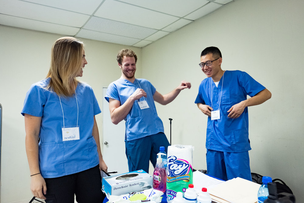 NYAGI volunteers, Rachel Ledesma (left), with Chris Paris (middle) and Kevin Xie (right), enjoying doctor jokes in between juggling the 500 or so patients NYAGI and the Haitian doctors practiced on throughout the week.