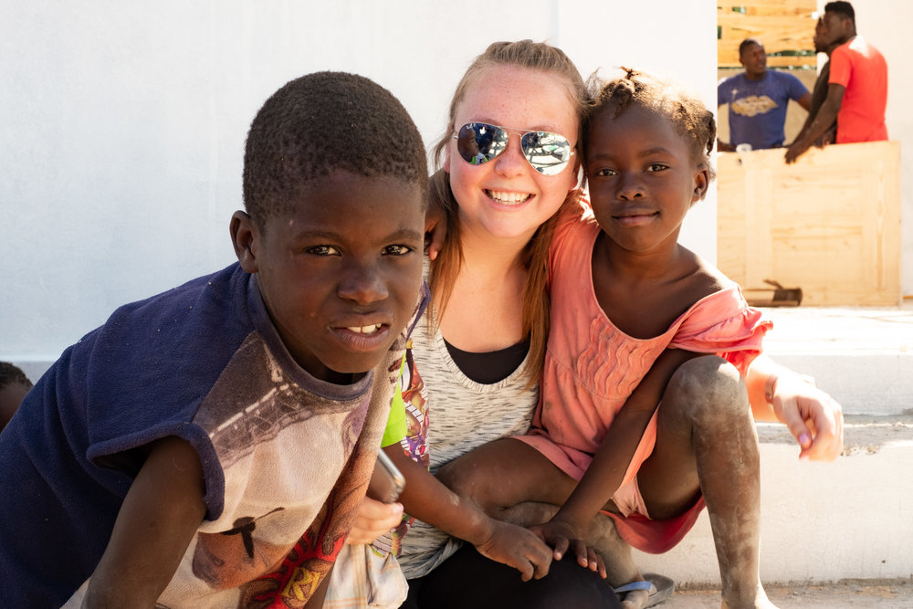 Medical Assistant, Becca Makens, with kids outside a new community center being built in Chambrun, just outside Port-au-Prince, Haiti.