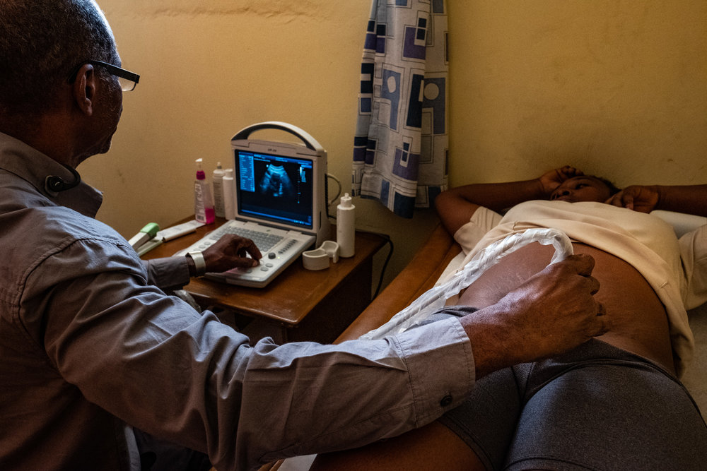 Dr. Arold Scutt, in his clinic just outside Port-au-Prince, Haiti, scanning a new mother after NYAGI skills-training.