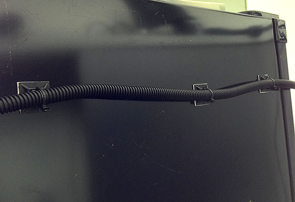 CAT5 cable inside split tube running to the front of the fridge.