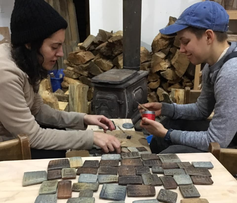 Laura and Silvia making magnets as work trade