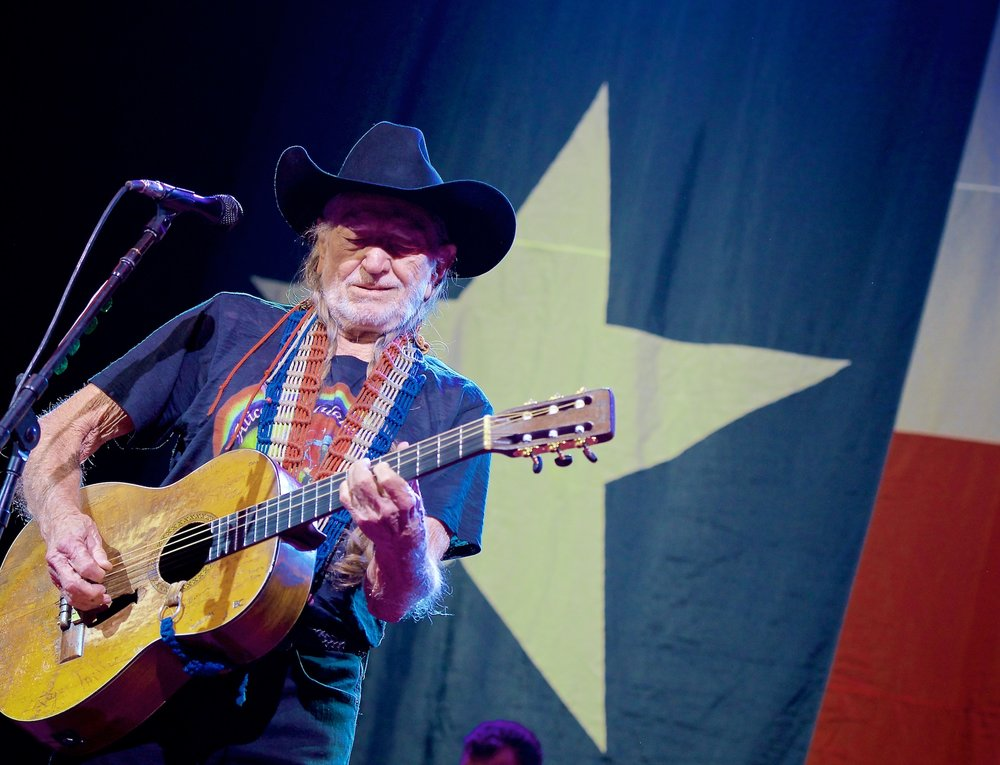 Willie Nelson performs in front of the Texas flag at House of Blues, Houston, November 18, 2014