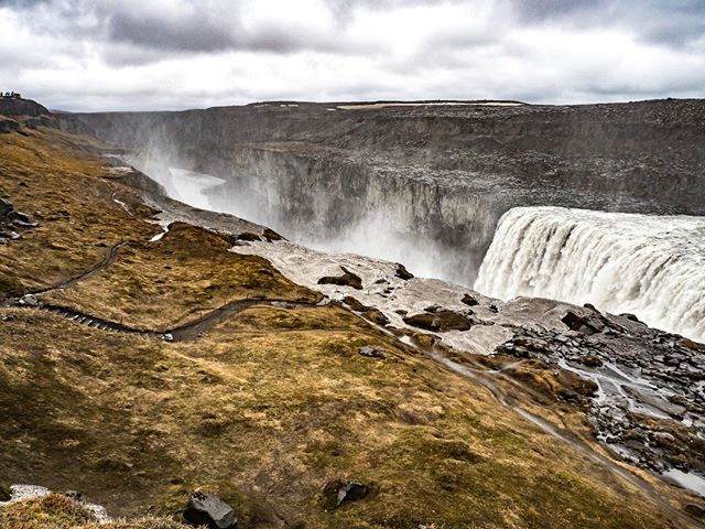 A blustery wind smacks my face whilst attempting to frame the roaring Dettifoss waterfall within the viewfinder of my camera. At 100 metres wide and 44 metres tall, it's difficult—if not impossible—to capture this beastly waterfall in a two-dimensional image. Not an uncommon frustration in Iceland.⁣ ⁣ But what blows my mind is the power of it all. The largest waterfall in Iceland in terms of sheer water flow, and one of the most powerful in Europe, Dettifoss in northern Iceland is capable of discharging 193 cubic metres of water per second; that's about 11 million litres of water per minute or enough water to fill one Olympic-sized swimming pool every 13 seconds.⁣ ⁣ Not that you'd want to swim here. Fed from the meltwater of Vatnajökull, the largest and most voluminous ice cap in Iceland, you're more likely to gasp for air than break any records swimming in this glacier-fed water. From that perspective, these chilly winds don't seem so bad at all.⁣ ⁣ I'm only a couple of hours into this full-day tour around Lake Mývatn and its surrounding region with @amazingnorth.is, and it's already apparent that, much like trying to capture Dettifoss in a photo, it's a Herculean task trying to squeeze the highlights of Lake Mývatn and its surrounding area into a single day. And yet, it hasn't stopped me from trying. ⁣ But you can't negotiate with the impossible. In 2012, Dettifoss was featured in the opening scene of Prometheus, a prequel to the Alien film series. But even with the famous American director Ridley Scott at the helm, the raw intensity of Dettifoss, and Lake Mývatn in general, cannot be captured in a film or in a photo. It needs to be experienced in the flesh—in all its raw glory.