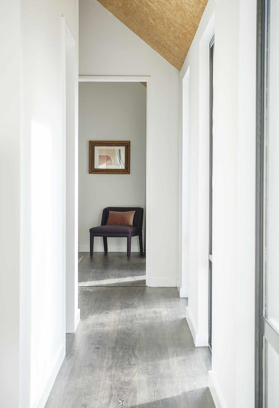 Master bedroom and hallway  In a corner of this room, an  Arthur G  armchair lets Izabela and Lukasz sit and admire the view and Lily Nicholson's artwork. All the flooring upstairs is 'Tally Oak' in Oiled Charcoal from  Aspecta Flooring .