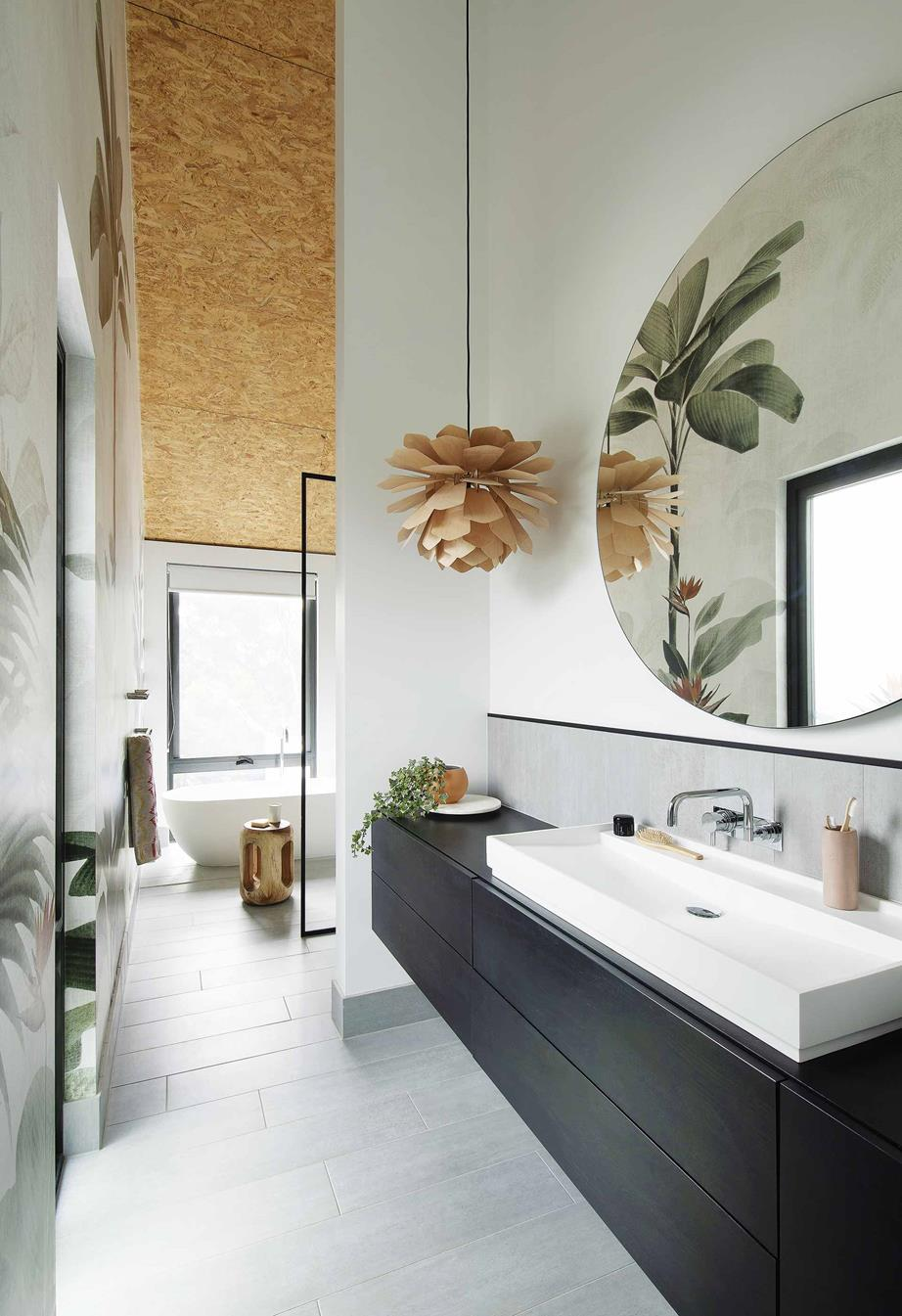 Ensuite  An oversized mirror from  The Block Shop  hangs above custom cabinetry imported from Poland and a basin from  Prodigg Bathrooms . Next to the Prodigg bath, a stool from  Empire Homewares  serves as a side table. The owners also imported the statement pendant light from Poland.
