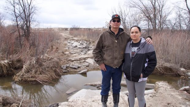 Pictured: Steve and Lacey Pourier standing on the road to their house on the Pine Ridge Reservation. The road is now rubble after they spent thousands to upgrade it.(Photo: Chuck Banner, Lakota People's Law Project)