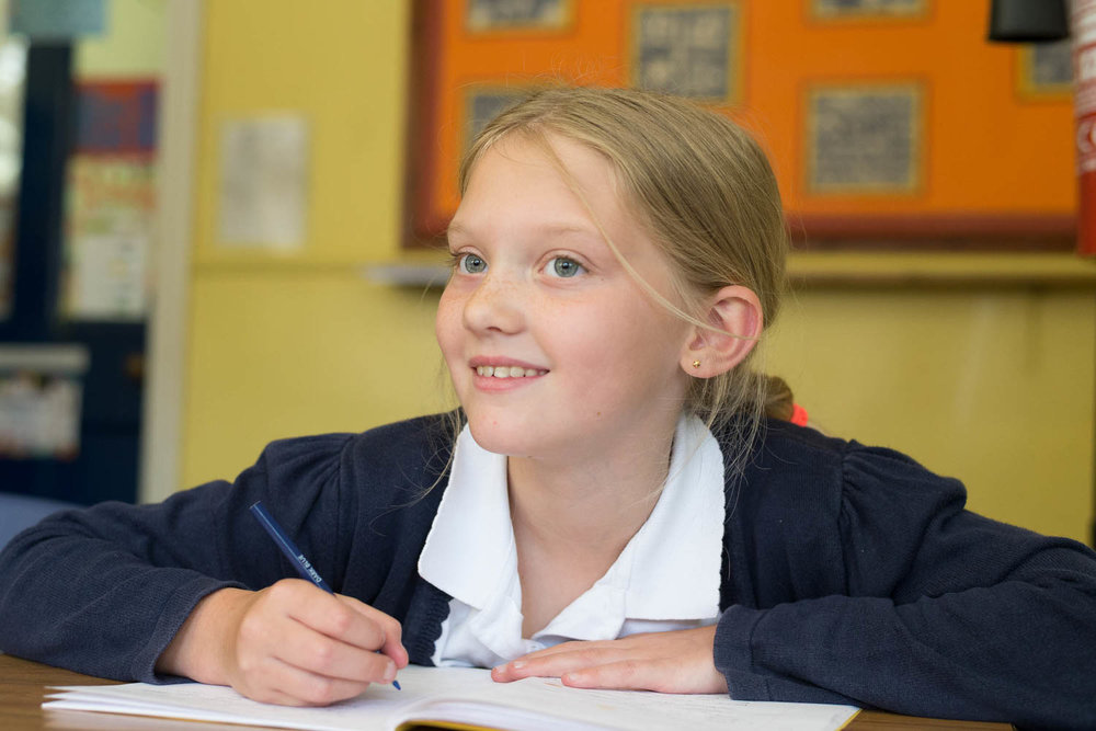 School girl at desk smiling
