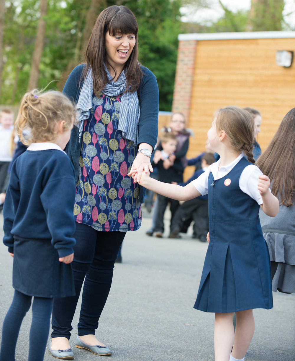 Teacher and children in playground