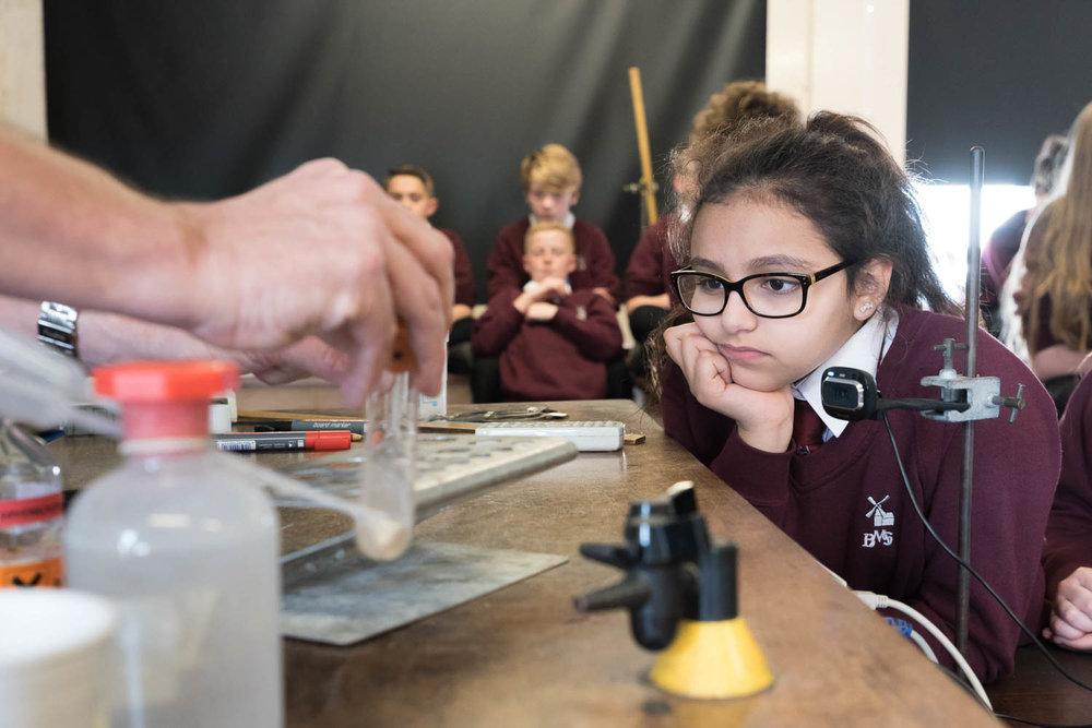 school girl watching science experiment