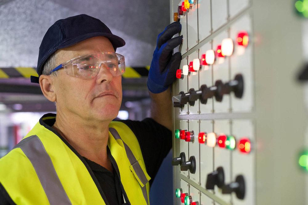 Workman in high viz looking at control board