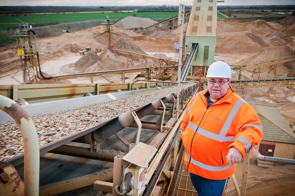 Worker poses at top of conveyor belt at Hanson quarry