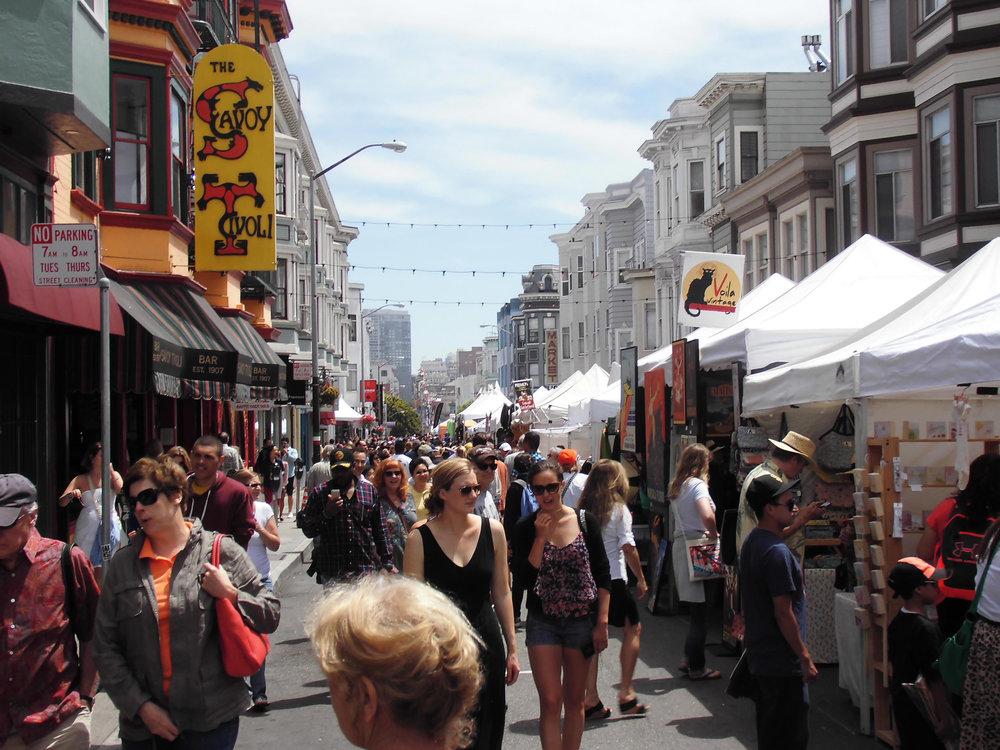 Visitors to the North Beach Festival explore vibrant Grant Street.