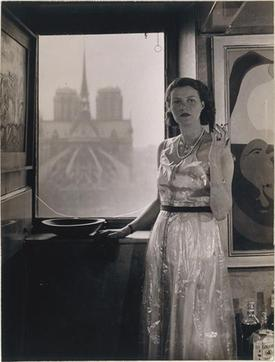 Peggy Guggenheim, Paris, c.1930, photograph Rogi André (Rosza Klein). In the background,  Notre Dame de Paris , and on the right,  Dutch Interior II  (1928) by  Joan Miró  (via Wikipedia)