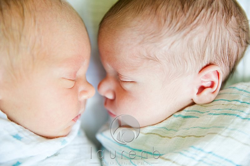 swaddled newborn twin boys faces noses