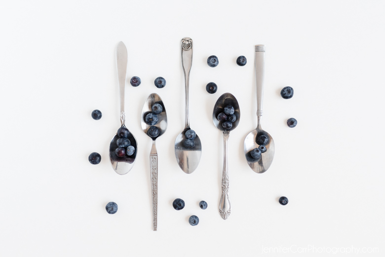 old antique spoons and blueberries in a fine art composition
