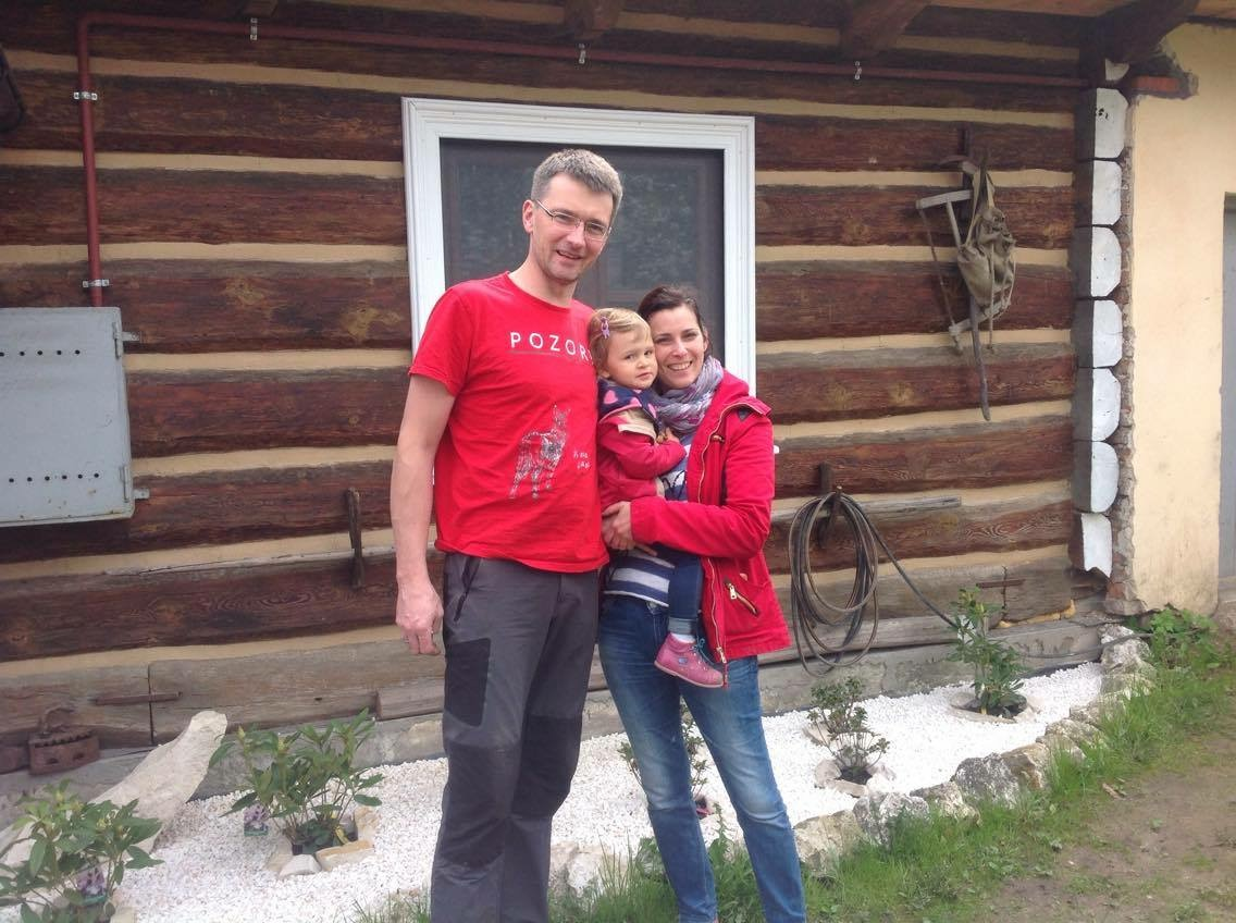 Dr. Drohobycka and family in front of their vintage log cabin currently under restoration