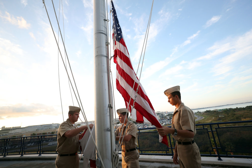 From left, Midshipman Dalton, Midshipman Cowdrey, and Midshipman Dastur begin to raise the flags for their morning formation on the sixth floor of the Texas A&M Maritime Academy Hall on Wednesday, Nov. 15, 2017. The cadets gather in formation in front of the dorm every day at 0715 to honor the flag and hear announcements from leadership.