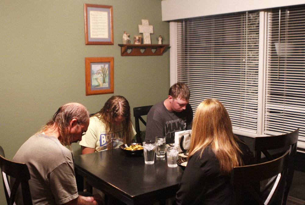 The Edquist family prays before dinner after a busy day. School and FFA activities occupy Hala, and Elias usually works until 8:00 p.m. The family makes it a point to eat supper together every day.