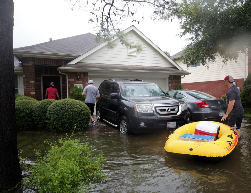 Cory Garcia, Jimmy Bishop and Carl Mundt enter Bishop's home in Bay Colony Pointe in Dickinson on Tuesday, Aug. 29, 2017. On August 27, 2017, Jimmy, Tiffany, Jacob and Joshua Bishop's home received at least 8 inches of water from Hurricane Harvey. It had receded on Tuesday, so the men went in to salvage anything they could.