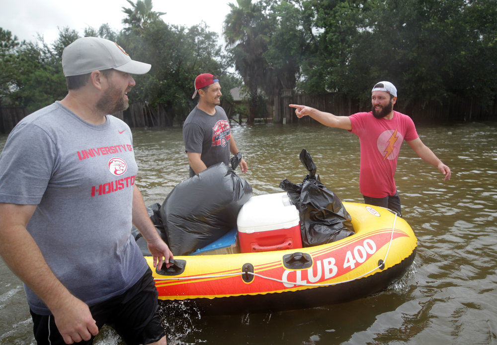 Cory Garcia points toward his home in Bay Colony Pointe in Dickinson and League City on Tuesday, Aug. 29, 2017. After grabbing salvageable items from Jimmy Bishop's home, the men floated their way down FM 646 toward their vehicle. The Bishop's stayed with some friends before moving to Tiffany Bishop's parents' home in Houston.