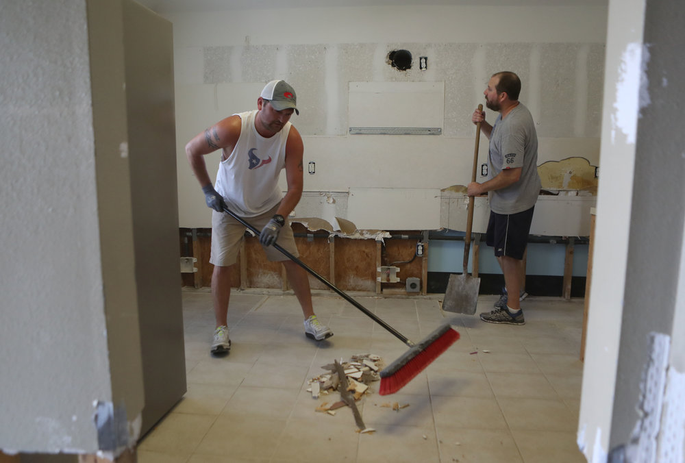 """Rob Haas sweeps debris as Jimmy Bishop looks at his empty kitchen at his home in Dickinson on Saturday, Sept. 23, 2017. """"We were lucky to know people that could help us,"""" Bishop said. The Bishops stayed with Tiffany's parents for nine months and friends helped them with a lot of the beginning processes."""