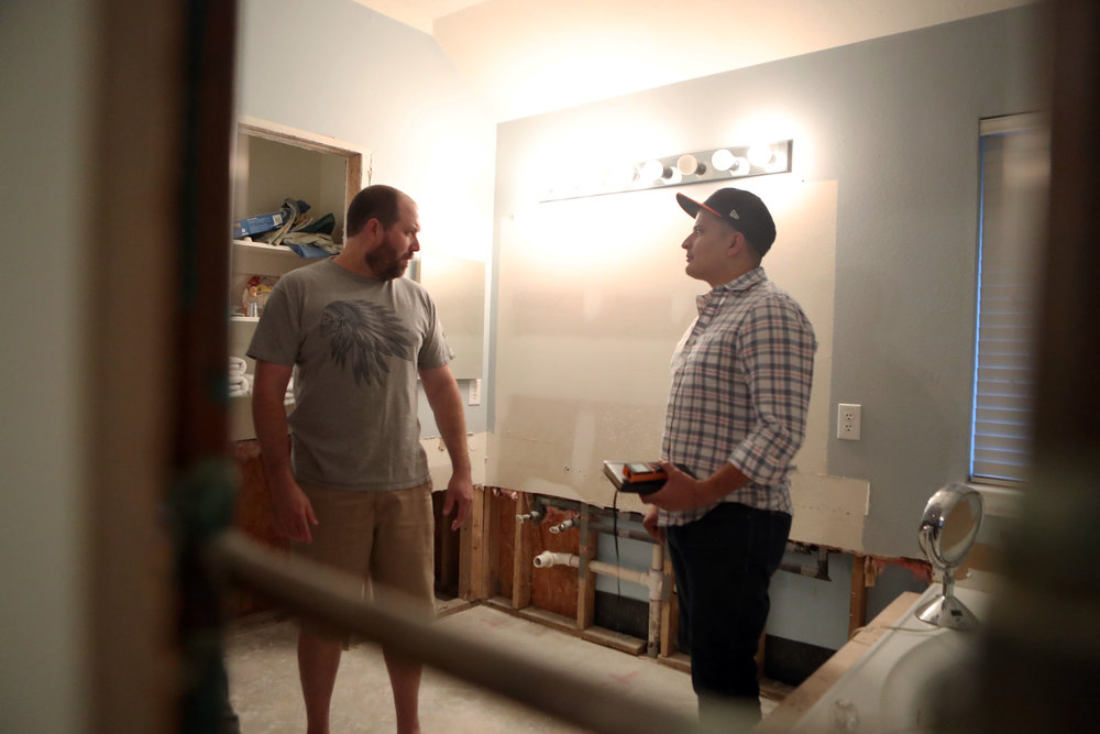"""Jimmy Bishop speaks with a contractor, Miguel Ortuno about the renovations they will need to make to the home on Tuesday, Oct. 17, 2017. Fixing the roof delayed the Bishop's renovations by at least a month, they said. Texas Wind Insurance Agency would not except their claim, despite ample roof damage. """"We thought if we paid our insurance, we would be able to get some help from them,"""" Tiffany said."""