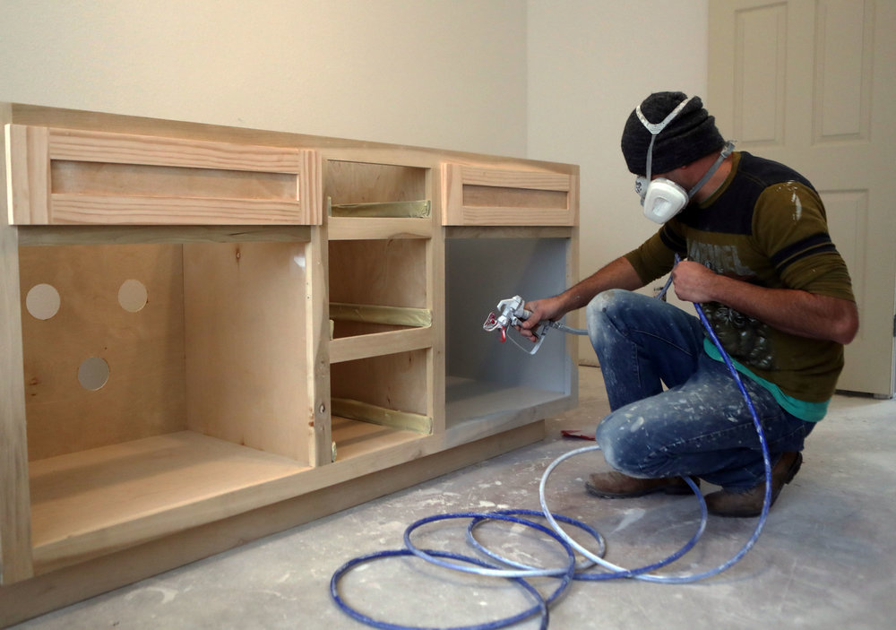 The Bishops' contractor Jesus Lopez spray paints a new dresser while working on their home in Dickinson on Thursday, Feb. 8, 2018. The Bishops found Lopez through other neighbors. Lopez was taking care of many of the houses in Bay Colony Pointe, so he had a pretty good idea of what to do in the house, they said.