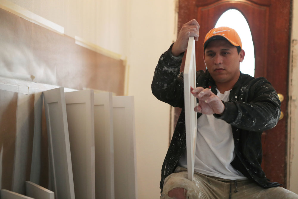 """William Campos checks the details in newly-sanded kitchen cabinets while working on the Bishops' home on Thursday, Feb. 8, 2018. The Bishops could choose every detail in their remodeled home. """"That is one positive of Harvey,"""" Tiffany said. """"We would have never renovated the house without it."""""""