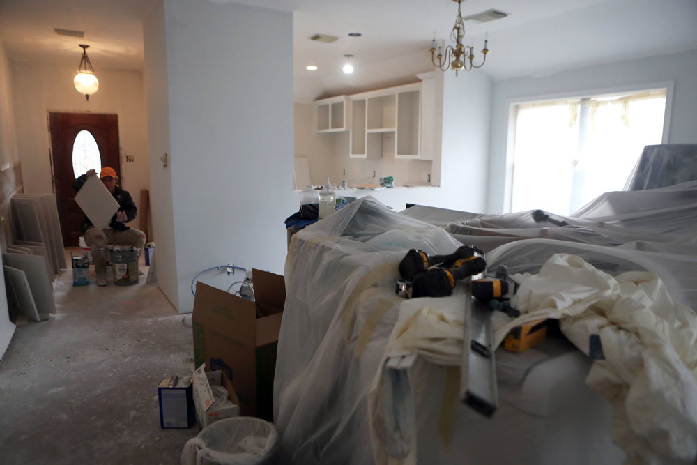 Furniture is covered by a tarp in the Bishops' living room while William Campos checks the sanding of new cabinets on Thursday, Feb. 8, 2018. While there were renovations, the contractors realized the Bishops had termite damage in the back of their house, which was something they would have never found without the flood.