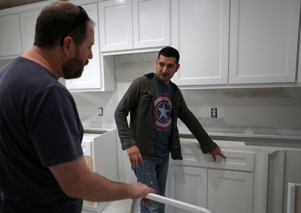 """Jesus Lopez shows Jimmy Bishop the new kitchen cabinets when Jimmy stopped by to be updated on Friday, March 2, 2018. """"Jesus did a great job for most things,"""" Jimmy said. """"There were a couple things that we wanted to change and some decisions were made for us, but he was easy to work with and did the best work he could."""""""