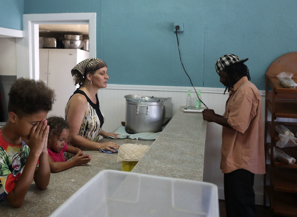 Karla White leads a prayer with Koa, middle, and Kenan, left, before serving lunch at the Streetscape Café on Thursday, May 24, 2018. The Whites have been operating Streetscape for two years and often lead Bible studies while people eat their breakfast or lunch.