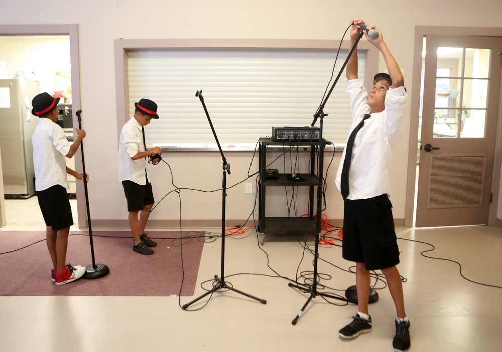 From left, Kilion, Kenan and Kemuel White take down the microphones and other equipment after their performance at the First Lutheran Church on Thursday, June 21, 2018. The Whites began playing music at the Wright Cuney Recreation Center five years ago and have continued to improve their skills together.