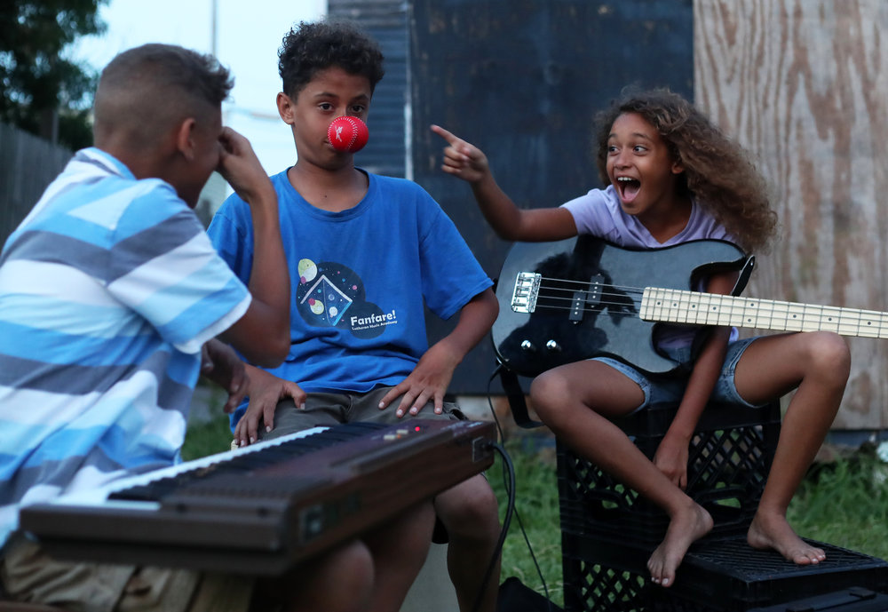 Keziah, right, and Kemuel, right, laugh at Kenan White before they play their instruments at their home in Galveston on Tuesday, June 5, 2018. The family tries to gather for a weekly bonfire where they rehash the day, have a family Bible study, practice music and worship God together.