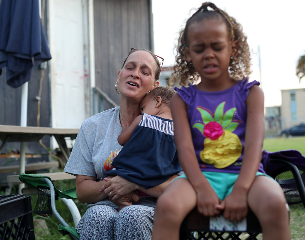 Karla and Koa White sing while Karla holds Kyla during at bonfire outside their home in Galveston on Tuesday, June 5, 2018. The bonfires give Karla the time to use music to worship with her children.