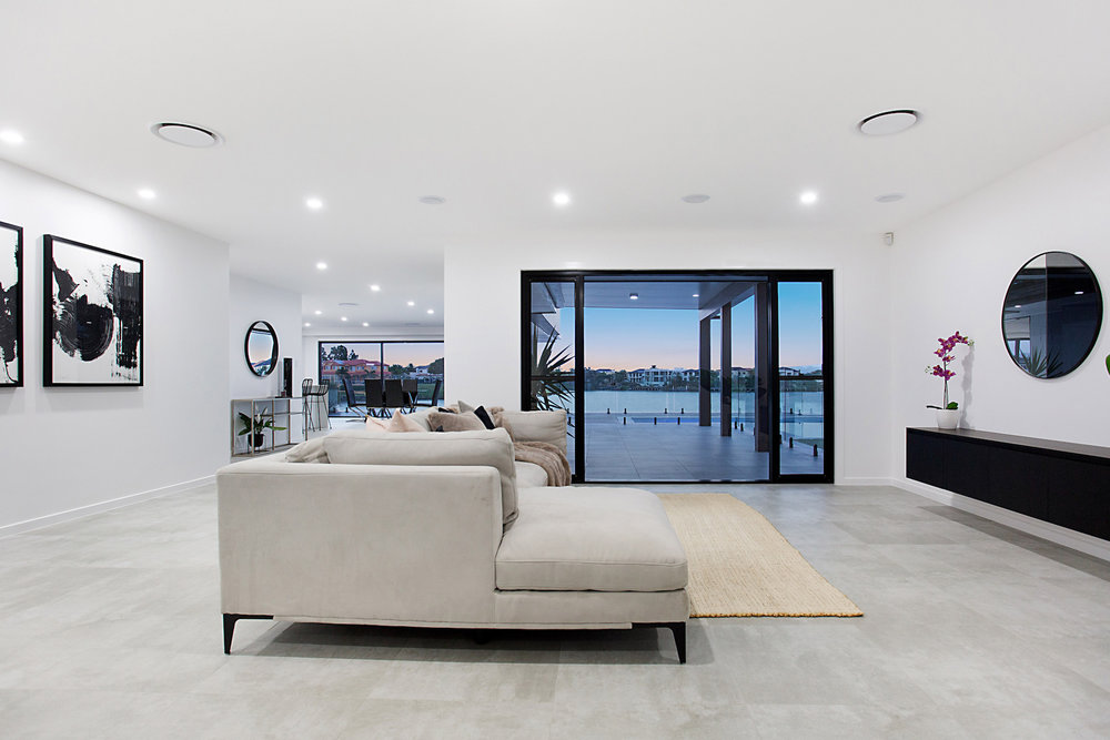 modern open plan living with high ceilings large windows and concrete tiles