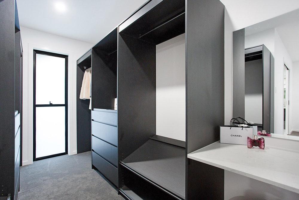 custom made modern black walk in robe with glass top display case draw