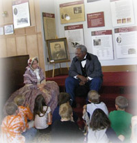 Volunteers interpret historic figures with a group of school children.