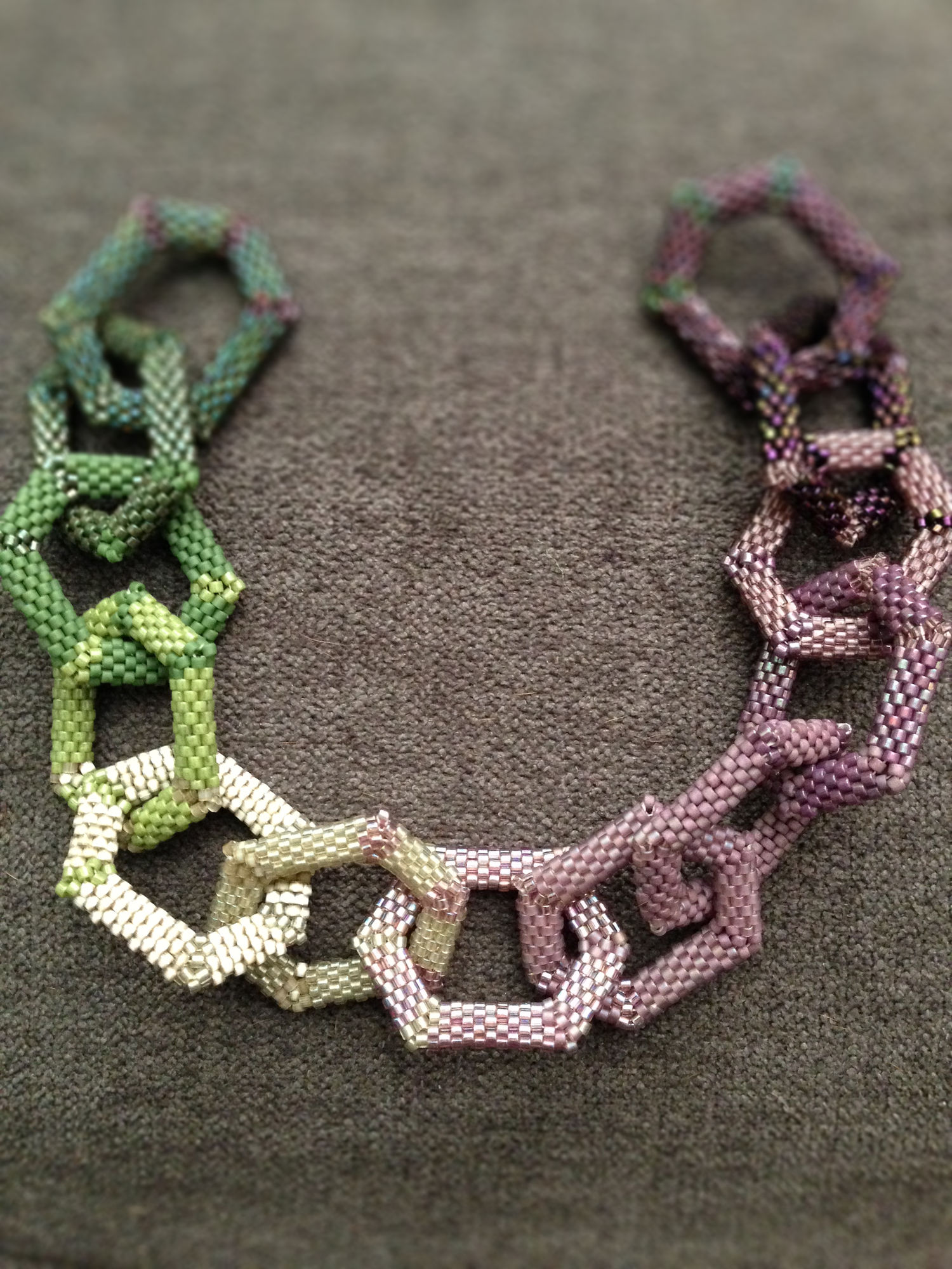 A string of peyote hexagons in a spectrum from dark green to light green to pale silver to lavender to dark purple.