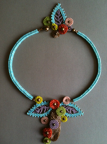 Blue herringbone necklace with pendant made of brick-stitched flowers and Russian leaf elements.