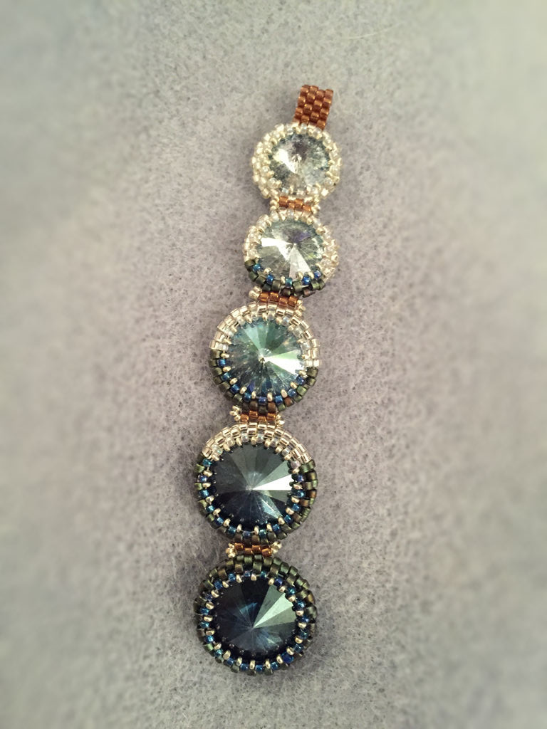 Pendant made from a series of Swarovski rivolis in dark and pale blue. Silver and blue beaded bezels mimic the progression of the phases of the moon, and bronze peyote strips connect the rivolis to one another in series.