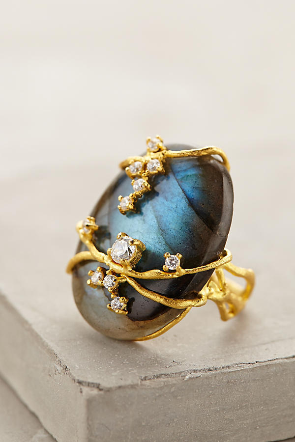 A blue labradorite cabochon is wrapped with gold vines. Small white diamonds glitter here and there on the vines.