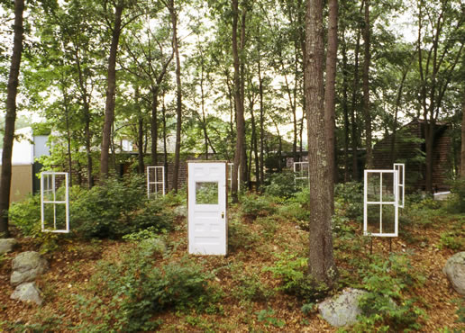 Ghost House - By diminishing the boundary between the architecture and its wooded site, this installation reveals both the humanly imagined and the dynamic natural aspects of the landscape. The installation also suggests the temporal and spatial tensions between them. Drawing on the imagery of ruins and abandoned buildings, the architectural fragments evoke the ghostly outlines of a vanished place and memories of an earlier time. However, these imagined outlines also enclose a dynamic physical landscape, a living forest, expanding and ever changing. Literally rooted in the present, this natural setting is defined by its architectural elements, but not displaced by them.Windows, Door, SteelApproximate Dimensions: 40' x 40' Installed - 1996Fuller Art Museum
